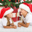 Laughing kids in front of christmas tree — Stock Photo