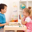 Kids playing board game in their room - Stock Photo