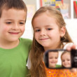 Say cheese - kids taking a photo of themselves - Stock Photo