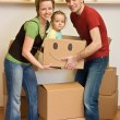 Happy family with a kid moving into a new home — Stock Photo