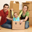 Happy family in their new home sitting on the floor — Stock Photo