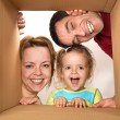 Family opening cardboard box - happy moving concept — Stock Photo