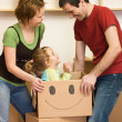 Happy couple with a kid unpacking in a new home — Stock Photo