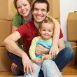 Happy family in their new home with lots of boxes — Stock Photo