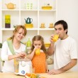 Family making and drinking fresh fruit juice - Stockfoto