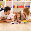 Happy family reading in the kids room — Stock Photo