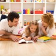 Happy family reading in the kids room — Stock Photo #6430449