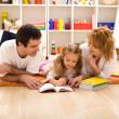 Happy family reading in the kids room — Stock Photo