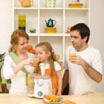 Happy healthy family drinking orange juice — Stock Photo #6430464