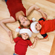 Woman and her kids on the floor at christmas — Stock Photo