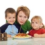Smiley family eating pasta — Stock Photo