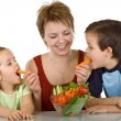 Happy kids eating vegetables — Stock Photo