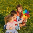 Woman and kids playing with a windmill toy — Stock Photo #6430576