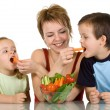 Woman feeding kids with vegetables — Stock Photo #6430583