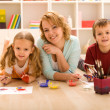 Woman and kids doing heavy artwork — Stock Photo