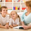 Kids having fun reading stories with their mom — Stock Photo