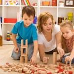 vrouw en kinderen spelen met houtblokken — Stockfoto