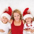 Woman and kids lating on the floor at christmas time — Stock Photo