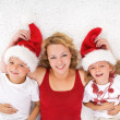 Woman and kids lating on the floor at christmas time — Stock Photo #6430617