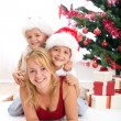Happy in front of christmas tree — Stock fotografie