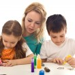 Kids busy painting with lots of colors - Stock Photo