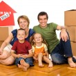 Happy family with cardboard boxes moving in a new home - Stock Photo
