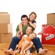 Happy couple with two kids in their new home — Stock Photo #6430716