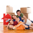 Happy family laying on the floor of their new home — Stock Photo