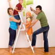 Stock Photo: Happy family with painting utensils repainting their home