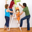 Stock Photo: Happy family redecorating the house - painting