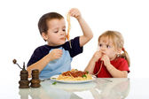 Two kids eating pasta with their hands — Stock Photo