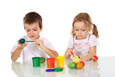 Boy and girl painting the easter eggs — Stock Photo