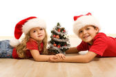 Kids on the floor with a decorated tree and christmas hats — Stock Photo
