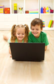 Kids with laptop laying on the floor — Stock Photo