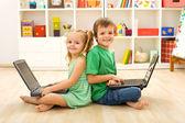 Happy kids with laptops sitting on the floor — Stockfoto