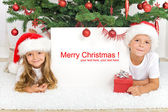 Kids laying under the christmas tree — Stock Photo