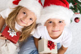 Kids with their christmas presents presents — Stock Photo