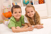 Little boy and girl listening to music together — Stock Photo