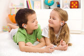 Kids sharing earphones listening to music — Stock Photo