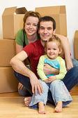 šťastná rodina sedí na podlaze v novém domově — Stock fotografie