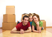 Happy family laying on the floor in their new home — Stock Photo