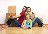 Famille heureuse dans leur nouvelle maison avec des boîtes en carton — Photo