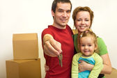 Family with the keys of their new home — Stock Photo