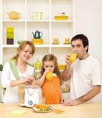 Familie machen und trinken saft aus frischen früchten — Stockfoto