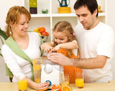 Family making fresh fruit juice together — Stock Photo