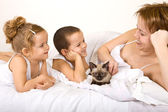 Woman and kids with a kitten lazying in the bed — Stock Photo