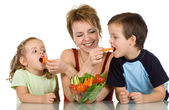 Woman feeding kids with vegetables — Stock Photo