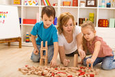 Woman and kids playing with wooden blocks — Stock Photo