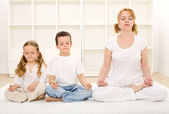 Family relaxing with yoga — Stock Photo