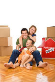 Happy couple with two kids in their new home — Stock Photo
